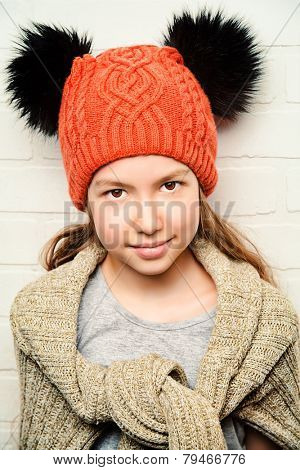 Cute smiling teenager girl wearing warm knitted sweater and knitted cap. Beauty, fashion. Seasonal clothing.