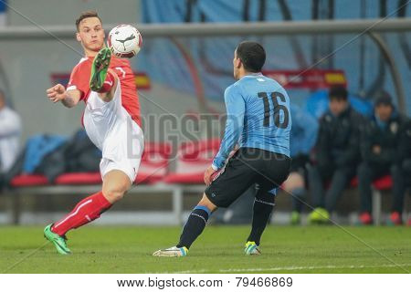 KLAGENFURT, AUSTRIA - MARCH 05, 2014: Marko Arnautovic (#7 Austria) and Maximilano Pereira (#16 Uruguay) fight for the ball in a friendly soccer game between Austria and Uruguay.