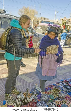 UYUNI, BOLIVIA, MAY 15, 2014:  Local woman in traditional attire sells handmade woolen caps to a tourist