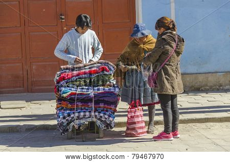 UYUNI, BOLIVIA, MAY 15, 2014:  Local women, one of them in traditional attire, buy blankets from street seller
