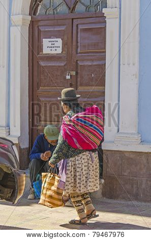 UYUNI, BOLIVIA, MAY 15, 2014:  Local woman in traditional attire walks at Plaza Arce