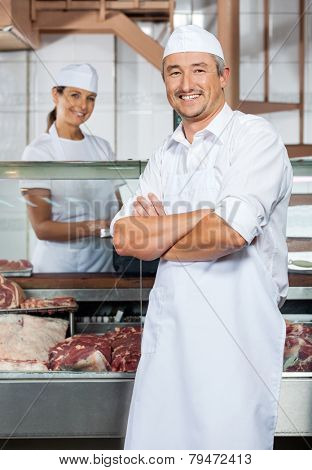 Portrait of confident mature male butcher with female colleague in background at shop
