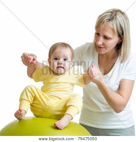 mother doing gymnastic to kid on fitness ball