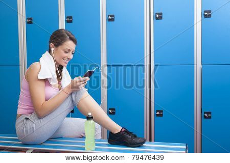 Fitness Smiling Woman Using Smart Phone In Dressing Room