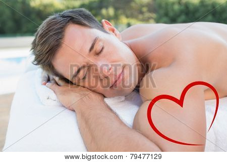 Peaceful man lying on massage table poolside against heart