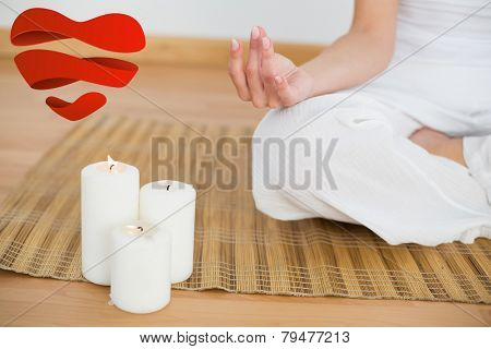 Woman sitting in lotus pose beside white candles against heart