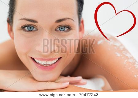 Peaceful brunette lying with salt scrub on back smiling at camera against heart