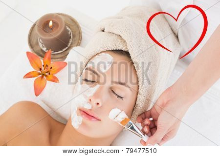 Attractive woman receiving treatment at spa center against heart