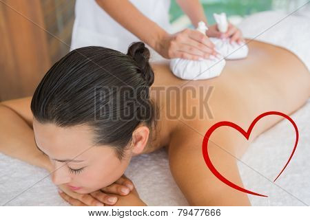 Content brunette getting a herbal compress massage against heart