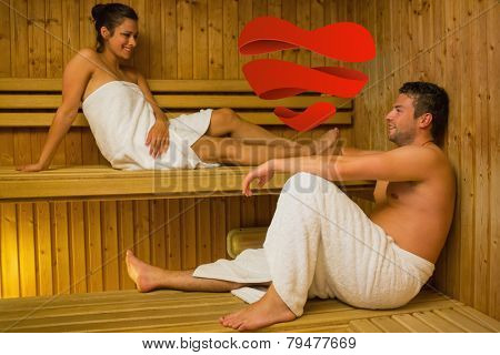 Happy couple relaxing in a sauna and chatting against heart