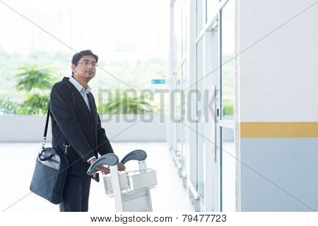Asian Indian businessman walking with airport trolley