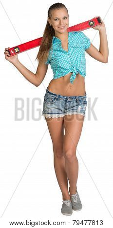 Pretty girl in shorts and shirt holding red building level of the neck. Full length