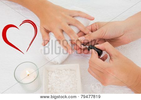 Nail technician painting customers nails against heart