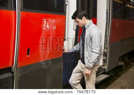 Handsome young man getting aboard on train