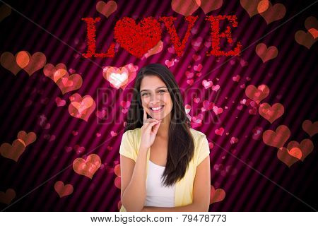 Happy casual woman thinking with hand on chin against digitally generated girly heart design