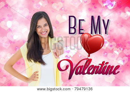 Happy casual woman pointing to camera against digitally generated girly heart design