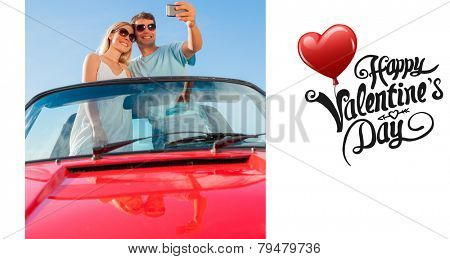 Smiling couple standing in red cabriolet taking picture against cute valentines message
