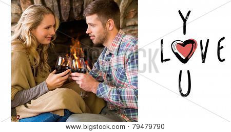 Couple toasting wineglasses in front of lit fireplace against cute valentines message