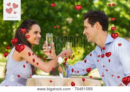 Couple with champagne flutes sitting at outdoor caf�?�© against cute valentines message