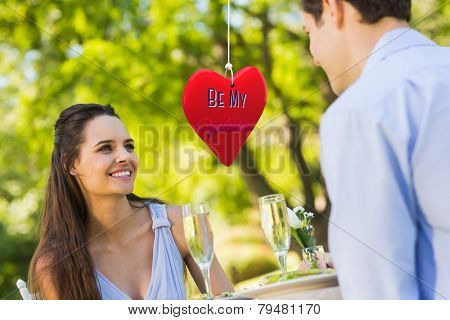 Couple with champagne flutes sitting at an outdoor caf�?�© against be my valentine