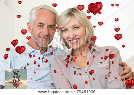 Smiling mature couple sitting on sofa with arm around against love is in the air
