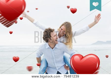 Man piggybacking woman at beach against heart label