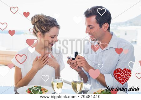 Man surprising woman with a wedding ring at lunch table against ich liebe dich