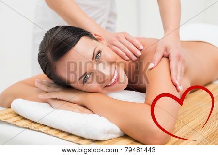 Beautiful brunette enjoying a shoulder massage smiling at camera against heart