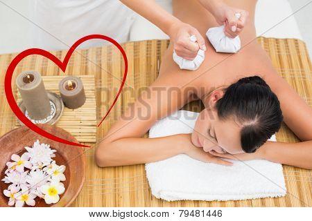 Peaceful brunette enjoying a herbal compress massage against heart