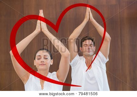 Peaceful couple in white doing yoga together with hands raised against heart