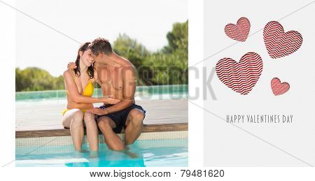 Gorgeous couple sitting poolside on holidays against cute valentines message