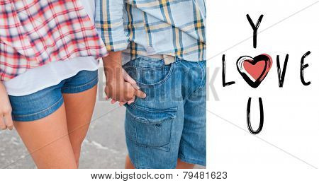 Couple in check shirts and denim holding hands against cute valentines message