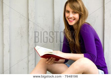 Teenage girl sitting with book