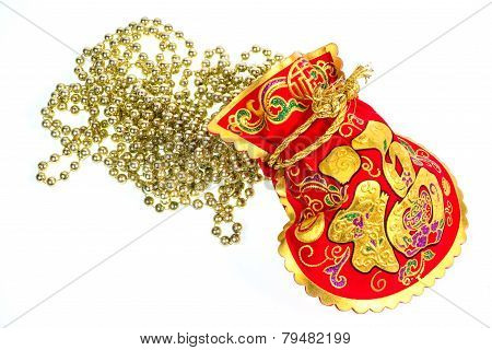 Red Gift Bags And Gold Ornamental Chain On White