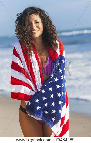 Beautiful young woman laughing wearing bikini and wrapped in American flag towel on a sunny beach