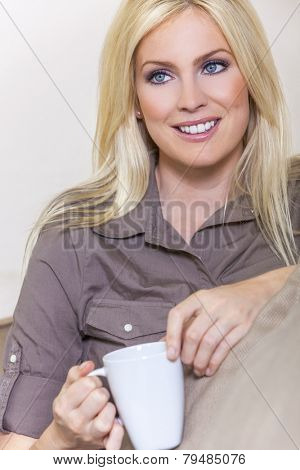A beautiful young blond woman drinking tea or coffee from a white mug sitting at home on a her sofa