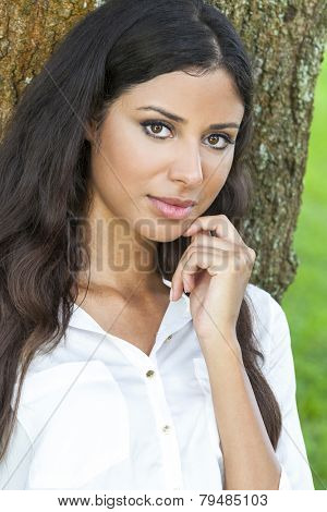 Outdoor portrait of a beautiful young Latina Hispanic girl or young woman leaning against a tree