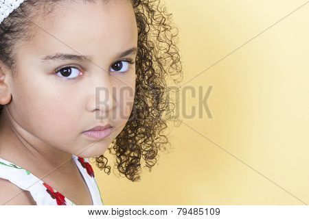 A beautiful mixed race African American little girl female child looking sad and sulking