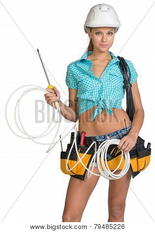 Pretty electrician in helmet, shorts, shirt, tool belt with tools holding screwdriver and an electri