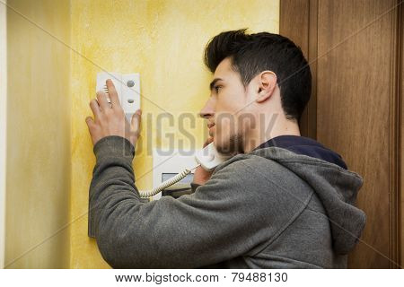 Young man answering the intercom in an apartment