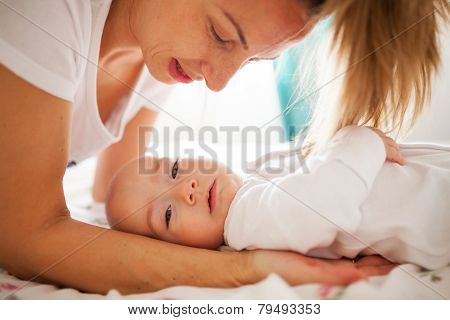 Mother Holding Baby On Bed