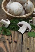 stock photo of crimini mushroom  - Champignon mushrooms in basketherbs and spices on a wooden background - JPG