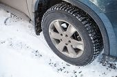 stock photo of stud  - Modern automotive wheel with studded tires and winter road - JPG