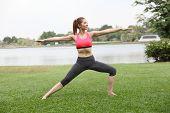 stock photo of virabhadrasana  - Yoga virabhadrasana II warrior pose by woman on lawnright side - JPG