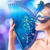 stock photo of incognito  - Young woman in venetian carnival blue mask with fan in hand in front of night city illumination - JPG