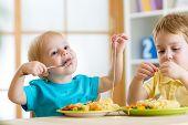 stock photo of kindergarten  - children boys eating healthy food in kindergarten or at home - JPG