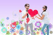 stock photo of girly  - Hipster couple smiling at camera holding a heart against digitally generated girly floral design - JPG