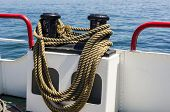 pic of bollard  - Boat with mooring rope around a bollard on board and view over the sea - JPG