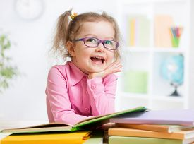 stock photo of nerd glasses  - Happy kid reading books and dreaming - JPG
