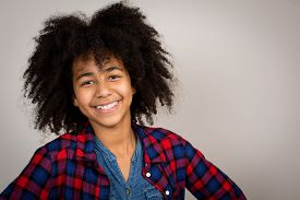 pic of wacky  - Portrait of a beautiful mixed race girl with wacky afro hair style laughing in a checkered shirt isolated against a grey background - JPG